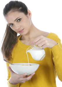 young-woman-pouring-milk-into-a-bowl